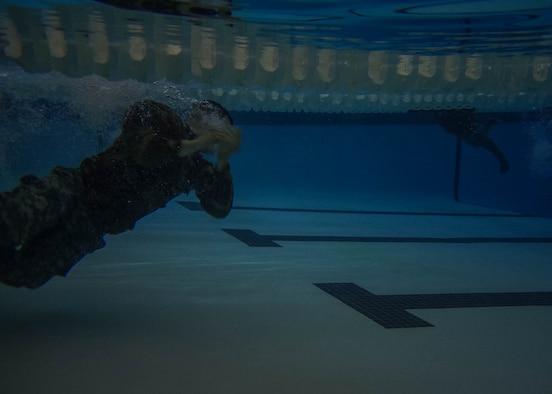 A U.S. Army Soldier struggles to remove his uniform during the underwater portion of the German Armed Forces Badge for military Proficiency (GAFBP) competition held at Fr. Drum, N.Y. on Saturday, march 11, 2017. The day began with 84 competitors and ended with 40 qualified finishers. The pool portion of the contest is where most participants were eliminated. (U.S. Air Force photo by Staff Sgt. Richard Mekkri)