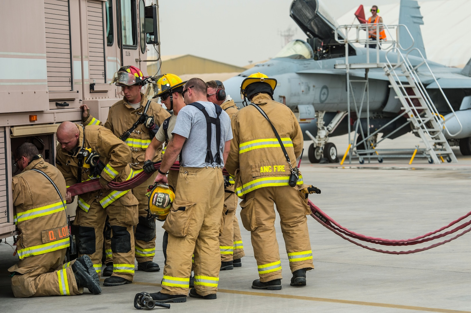 U.S. Air Force 380th Expeditionary Civil Engineer Squadron firefighters and Royal Australian Air Force firefighters store equipment on a firetruck after completing a Coalition training exercise at an undisclosed location in Southwest Asia, March 16, 2017. USAF and RAAF firefighters have completed weekly exercises for nearly three months while supporting Operation Inherent Resolve. The training scenarios have developed critical firefighting fundamentals required during deployed day-to-day operations. (U.S. Air Force photo/Senior Airman Tyler Woodward)
