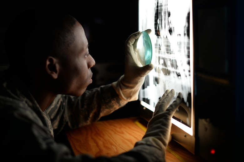 A 48th Equipment Maintenance Squadron nondestructive inspection journeyman examines x-ray film of an F-15 Eagle component on Royal Air Force Lakenheath, England, March 10, 2017. NDI Airmen are able to inspect aircraft for defects without having to deconstruct them completely, saving valuable time and money. (U.S. Air Force photo/Staff Sgt. Emerson Nuñez)