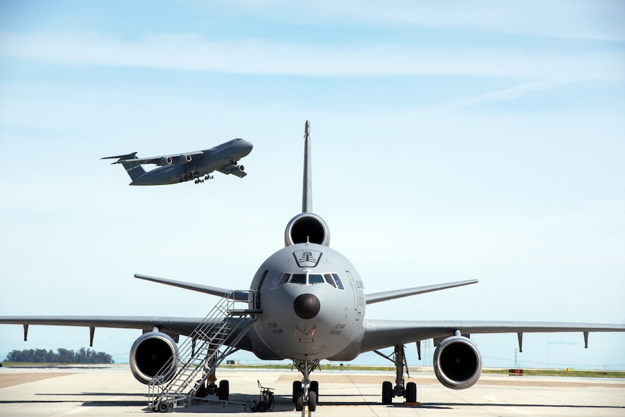 A KC-10 Extender is parked on the ramp as a C-5M Super Galaxy takes off at Travis Air Force Base, Calif., Mar. 16, 2017. (U.S. Air Force photo by Louis Briscese)
