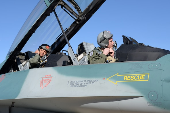U.S. Air Force pilot, Capt. Sean Rush (front) and Indonesian Air Force pilot, Maj. Gusti Made Yoga Ambara (rear), strap on thier helmets at Hill Air Force Base, Utah on March 14 in preparation for the long transoceanic flight to Indonesia. The flight is expected to take four days with schedluded stops enroute.  (U.S. Air Force Photo by Alex R. Lloyd)