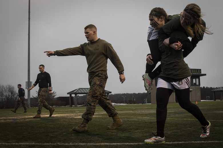 Isabell Smith, a freshman at Husson University and player with the Women Lacrosse Team, fireman-carries a teammate during the maneuver under fire portion of the Combat Fitness Test during a Leadership Seminar with Marine recruiters from Recruiting Substations Central and Northern Maine, March 8. The lacrosse team was run through the CFT, a series of circuit course exercises and activities, and a seminar on Marine Corps leadership traits and principles.