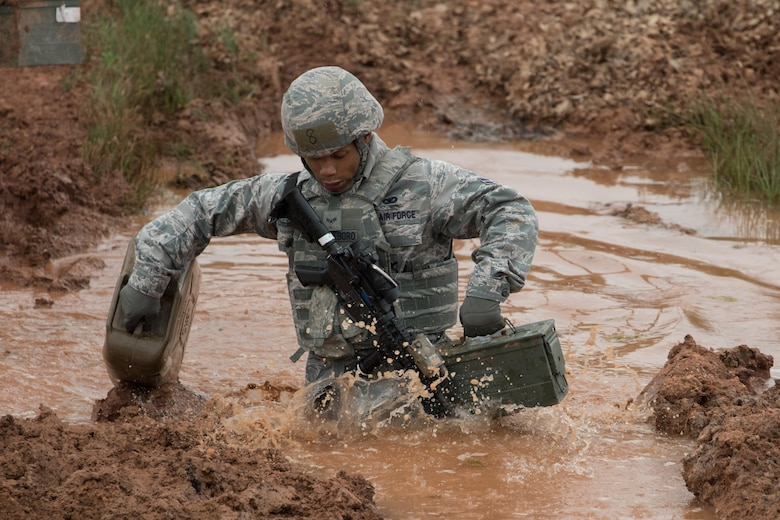 U.S. Air Force Airman 1st Class Noel Cheeseboro, 7th Security Forces member, walks through a mud pit with a jug of water and an ammo can during a resupply challenge March, 11, 2017, at Dyess Air Force Base, Texas. The Top Defender Challenge tested the 7th SFS member's ability to work together as two-man teams to accomplish different tasks. (U.S. Air Force Photo by Tricia Bruton)