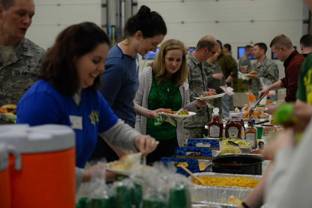 """Members of Team Mildenhall prepare their plates during Hearts Apart March 16, 2017, at the fire department on RAF Mildenhall, England. This month's theme was based on St. Patrick's Day. Participants enjoyed free food, a bouncy castle, photos with a """"Leprechaun"""" and a magic show. (U.S. Air Force photo by Staff Sgt. Micaiah Anthony)"""