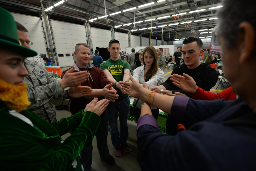 """Members of Team Mildenhall participate in a physical challenge conducted by magician Eric """"El Rico"""" Armstrong, far right, during Hearts Apart March 16, 2017, at the fire department on RAF Mildenhall, England. This month the 100th Aircraft Maintenance Squadron hosted the monthly event which helps bring Team Mildenhall families closer together during times of separation. (U.S. Air Force photo by Staff Sgt. Micaiah Anthony)"""