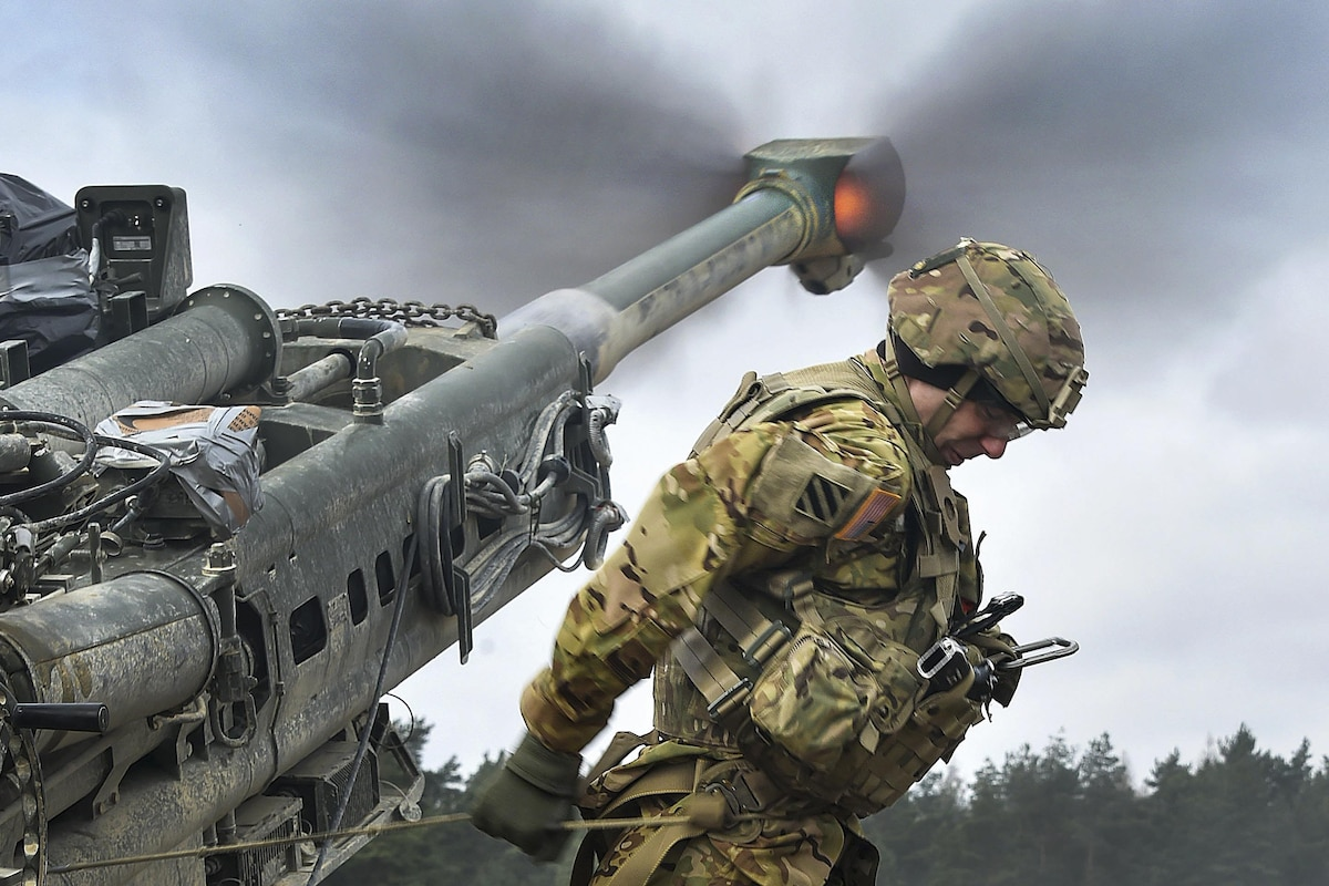 A soldier pulls the lanyard on a howitzer during a live-fire exercise.