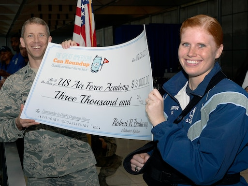 "Col. John Price, commander, commandant of cadets (left) and Cadet 1st Class Madison Martin, hold up a ""check"" for $3,000 March 16, 2016 at the U.S. Air Force Academy's staff tower in Mitchell Hall. The money was awarded to the Academy by the Can Manufacturers Institute for cadets taking first place in last year's Great American Can Roundup Recycling Challenge, a collegiate event across the U.S. Academy cadets beat-out all U.S. colleges and service academies by recycling more than 3,500 pounds of aluminum cans. (U.S. Air Force photo/Jason Gutierrez)"