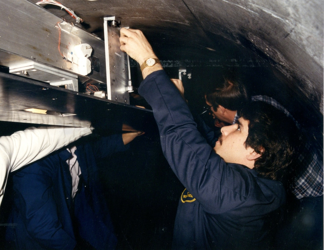 : Dan Marren, front, works as part of a test team on the first aero-optical experiment in the Hypervelocity Wind Tunnel 9, then operated by the Naval Surface Warfare Center, in support of the Strategic Defense Initiative Program in 1984. The innovative test measured precise optical aberrations of target signals presented to interceptor seekers travelling at Mach 10 which enabled the realization of ballistic missile defensive test capabilities used worldwide. Hypervelocity Wind Tunnel 9, located at the Federal Research Center in White Oak, Maryland, is now operated by AEDC. Marren, who is the director of the AEDC White Oak site was recently selected to receive the 2017 American Institute of Aeronautics and Astronautics Ground Testing Technical Committee's Ground Testing Award. (U.S. Navy photo)