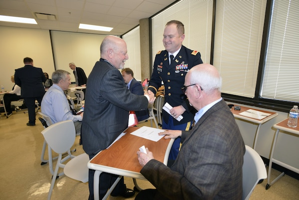 Maj. Christopher Burkhart, U.S. Army Corps of Engineers Nashville District deputy commander, welcomes Allen Scott of Wisdom Tree Technologies during the speed dating portion of the 6th Annual Small Business Industry Day at the Tennessee Small Business Development Center at Tennessee State University in Nashville, Tenn., March 15, 2017. The major and Roy Rossignol (seated), Nashville District Small Business chief, met with small business leaders during this matchmaking engagement.