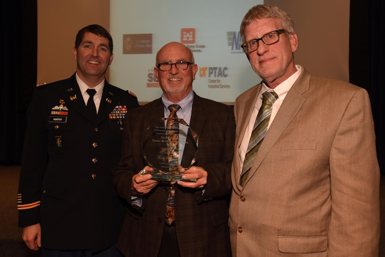 Russell Toone (Right), Procurement Technical Assistance Center in Jackson, Tenn., presents an award to Roy Rossignol (Center), U.S. Army Corps of Engineers Nashville District Small Business chief, during the 6th Annual Small Business Industry Day at the Tennessee Small Business Development Center at Tennessee State University in Nashville, Tenn. The award recognized Rossignol as the small business advocate of the year.  Lt. Col. Stephen Murphy, Nashville District commander, joined Rossignol for the presentation.