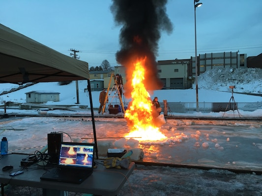 U.S. Army Engineer Research and Development Center's Cold Regions Research and Engineering Laboratory engineers hosted Applied Research Associates Inc. testing onsite using the Geophysical Research Facility, an outdoor refrigerated basin, to measure burn efficiency of oil in ice. In the foreground a computer screen visually monitors and streams the testing live to sponsors. In the background, researchers use visible and infrared cameras to measure thermal properties.