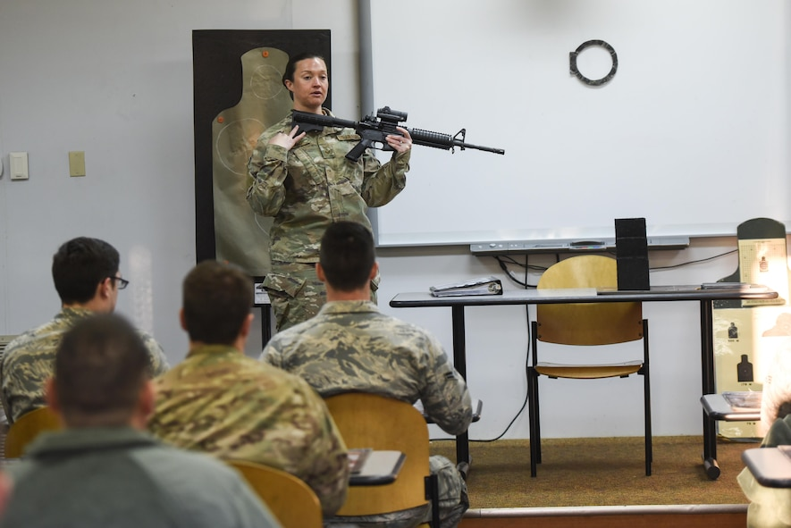 Staff Sgt. Elizabeth Marino, a Combat Arms Training and Maintenance instructor with the 1st Special Operations Security Forces Squadron, demonstrates how to properly hold an M4 rifle during a weapons qualification course at Hurlburt Field, Fla., March 16, 2017. Combat Arms Training and Maintenance instructors train and qualify Airmen on required weapons needed for deployments. (U.S. Air Force photo by Senior Airman Jeff Parkinson)