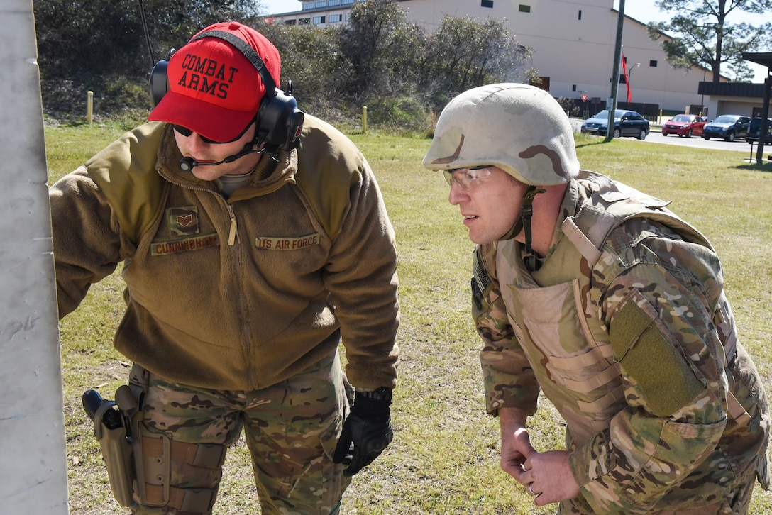 SSgt Cory Cunningham, a Combat Arms Training and Maintenance instructor with the 1st Special Operations Security Forces Squadron, evaluates Master Sgt. Derek Zarnesky's target during a weapons qualification course at Hurlburt Field, Fla., March 16, 2017. Combat Arms Training and Maintenance instructors train and qualify Airmen on required weapons for deployments. (U.S. Air Force photo by Senior Airman Jeff Parkinson)