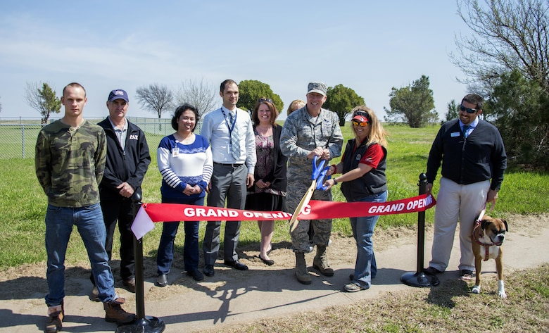 Brig. Gen. Patrick Doherty, 82nd Training Wing commander, along with Elizabeth Clements, Outdoor Recreation director, and other members of Team Sheppard, cut the ribbon during the grand reopening of the dog park at Wing Creek Park on Sheppard Air Force Base, Texas, March 15, 2017. (U.S. Air Force photo by Senior Airman Robert L. McIlrath/Released)