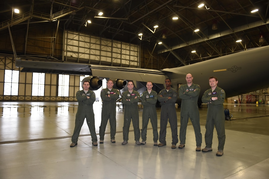 A group of seven Mobility Guardian planners stand in front of a C-17 Globemaster III in a McChord Field hangar at Joint Base Lewis-McChord, Wash., March 15, 2017. The group coordinated an airspace plan for Air Mobility Command's Mobility Guardian exercise that will take place here at JBLM this summer. (U.S. Air Force/Staff Sgt. Naomi Shipley)