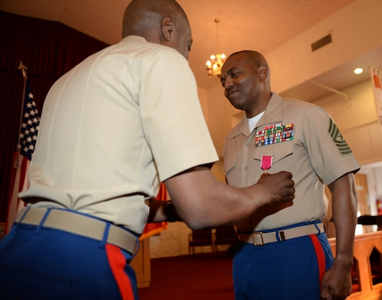 Sgt. Maj. Kenneth V. Agee, former sergeant major, Marine Corps Logistics Base Albany, receives a Legion of Merit from Col. James C. Carroll III, commanding officer, during a retirement ceremony at the Chapel of the Good Shepherd, here, March 16.
