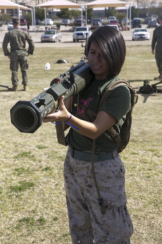 The wife of a Marine with 3rd Battalion, 4th Marines, 7th Marine Regiment, holds an M136 AT4 trainer at Del Valle Field during the battalion's Jane Wayne Day aboard Marine Corps Air Ground Combat Center, Twentynine Palms, Calif., March 8, 2017. (U.S. Marine Corps photo by Cpl. Julio McGraw)