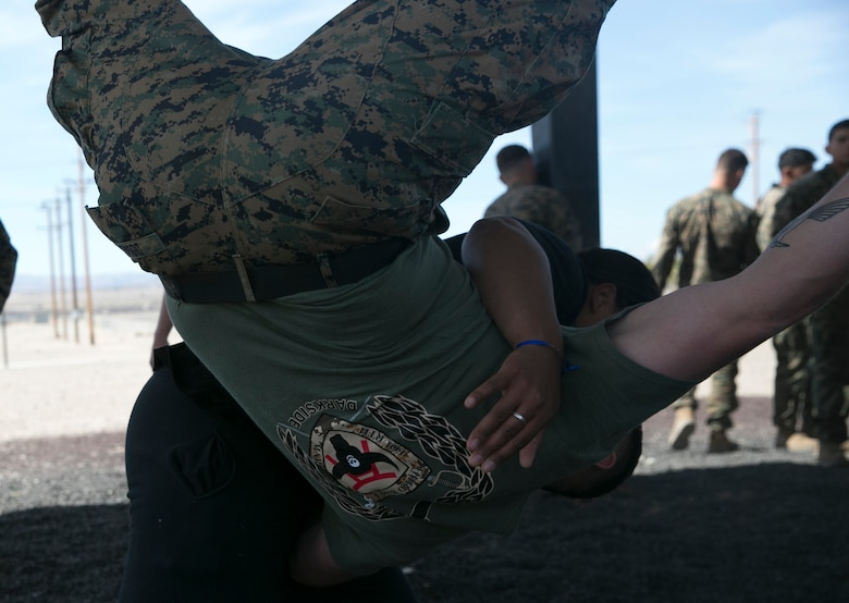 The wife of a Marine with 3rd Battalion, 4th Marines, 7th Marine Regiment, hip-tosses her husband during the Marine Corps Martial Arts Program instruction at Del Valle Field during the battalion's Jane Wayne Day aboard Marine Corps Air Ground Combat Center, Twentynine Palms, Calif., March 8, 2017. (U.S. Marine Corps photo by Cpl. Julio McGraw)