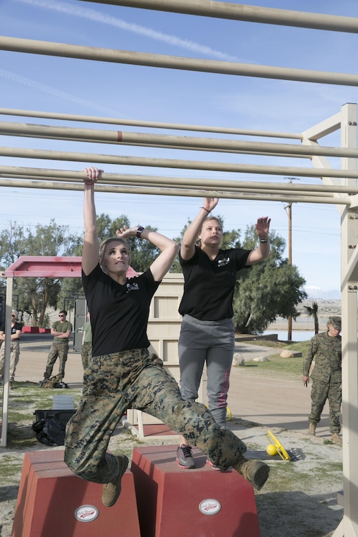 The wife of a Marine with 3rd Battalion, 4th Marines, 7th Marine Regiment, swings through the tactical monkey bars at the High Intensity Tactical Training obstacle course at Del Valle Field during the battalion's Jane Wayne Day aboard Marine Corps Air Ground Combat Center, Twentynine Palms, Calif., March 8, 2017. (U.S. Marine Corps photo by Cpl. Julio McGraw)