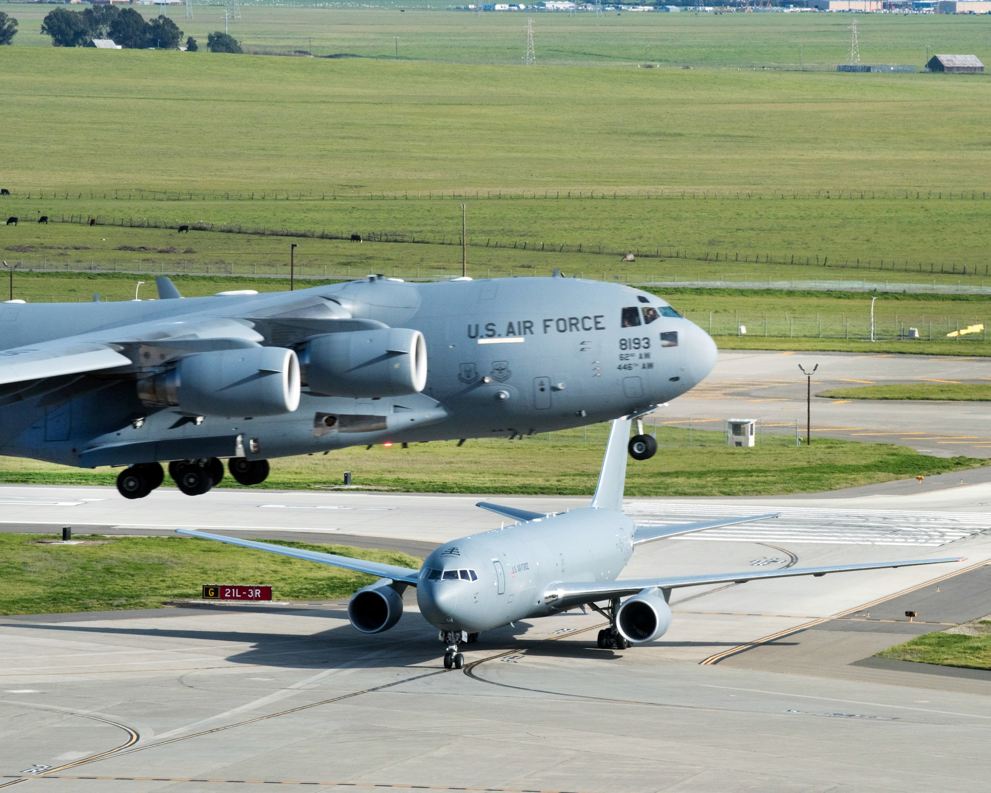 A Boeing KC-46A Pegasus arrives at Travis Air Force Base, Calif. while as C-17 Globemaster III takes off, Mar. 7, 2017. Travis was selected as a preferred location for the Air Force's newest refueling aircraft in January. This is the first time the aircraft has flown at an Air Mobility Command base and is scheduled to complete ground and flight testing during its time at Travis. (U.S. Air Force photo by Louis Briscese)
