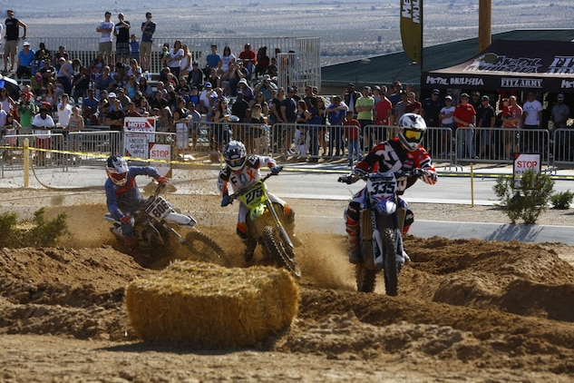 Three riders race against each other in the second race during the Motocross Jam Fest at 13th and Dunham aboard Marine Corps Air Ground Combat Center, Twentynine Palms, Calif., March 11, 2017. Marine Corps Community Services hosts the Motocross Jam Fest annually to provide Combat Center patrons with the opportunity to enjoy time out with their family and friends.  (U.S. Marine Corps photo by Lance Cpl. Natalia Cuevas)