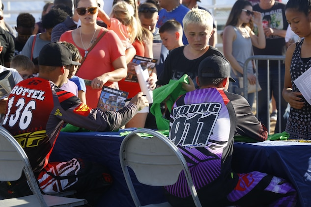 The racers sign autographs after the Motocross Jam Fest, at 13th and Dunham aboard Marine Corps Air Ground Combat Center, Twentynine Palms, Calif., March 11, 2017. Marine Corps Community Services hosts the Motocross Jam Fest annually to provide Combat Center patrons with the opportunity to enjoy time out with their family and friends. (U.S. Marine Corps photo by Lance Cpl. Natalia Cuevas)