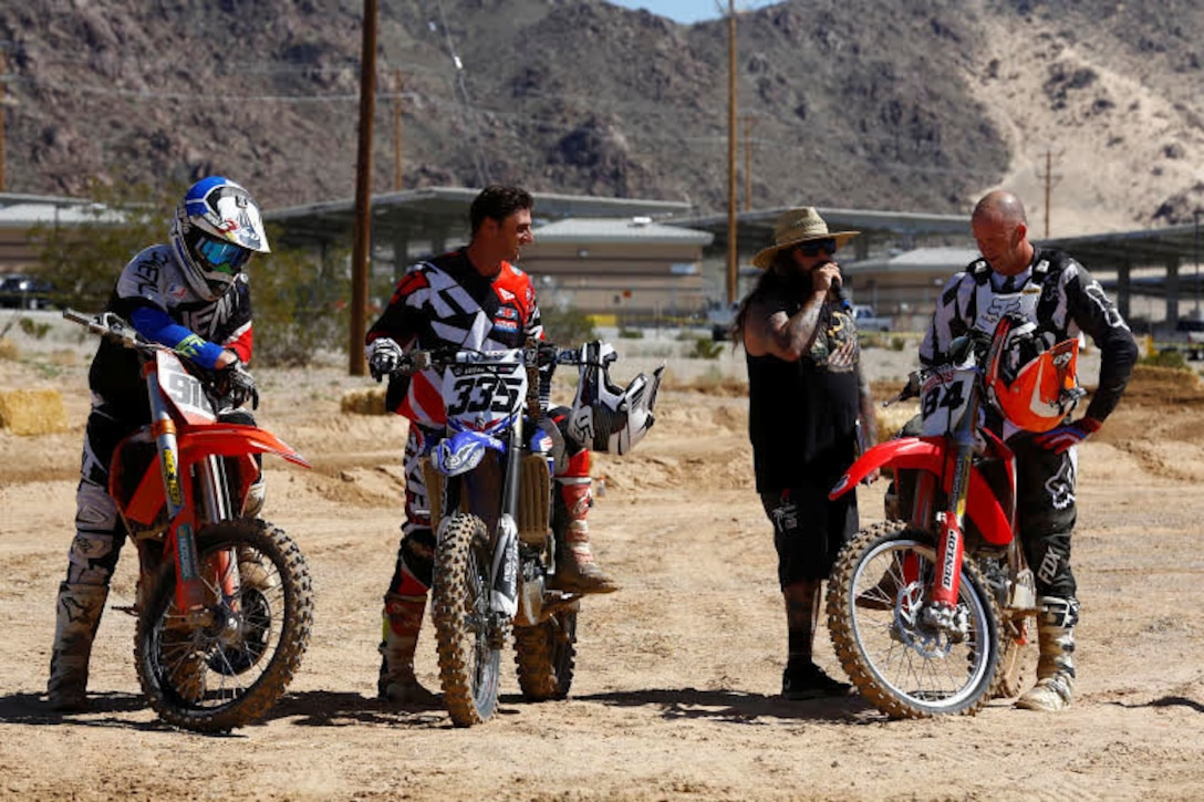 The Master of Ceremonies congratulates John Jelderda, Dennis Stapleton and Jeremy McCool, winners of the Motocross Jam Fest, at 13th and Dunham aboard Marine Corps Air Ground Combat Center, Twentynine Palms, Calif., March 11, 2017. Marine Corps Community Services hosts the Motocross Jam Fest annually to provide Combat Center patrons with the opportunity to enjoy time out with their family and friends.  (U.S. Marine Corps photo by Lance Cpl. Natalia Cuevas)