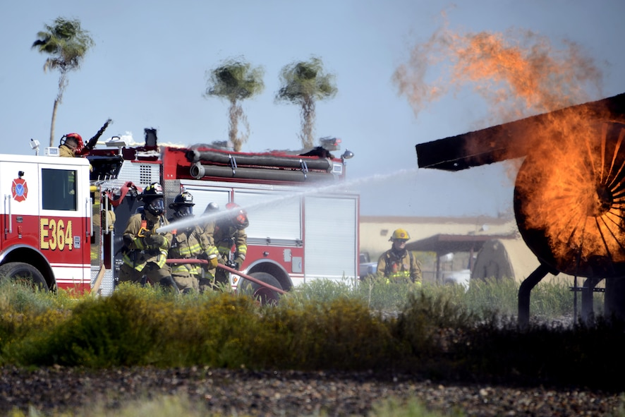 56th Civil Engineer Squadron firefighters and the Scottsdale Fire Department work together to put out a fire during a training exercise Mar. 16, 2017 at Luke Air Force Base, Ariz. The firefighters were training to respond to an aircraft fire. (U.S. Air Force photo by Senior Airman Devante Williams)