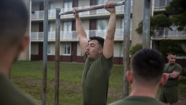 Cpl. Richard Flores, a training non-commissioned officer with Headquarters Battalion, demonstrates a proper pull-up technique prior to conducting a Physical Fitness Test at Marine Corps Base Hawaii, March 14, 2017. The PFT is an evaluation conducted throughout the Marine Corps annually to assess the level of fitness of Marines. For more information on the PFT updates, utilize Marine Corps Bulletin 6100.