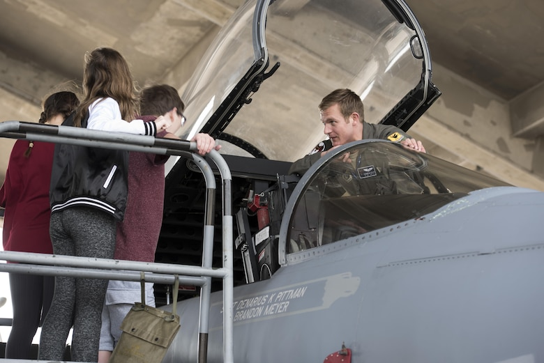 U.S. Air Force 1st Lt. Brock McGehee, 44th Fighter Squadron F-15 Eagle pilot, shows Kadena Middle School students the cockpit of an F-15C Eagle, March 3, 2017, at Kadena Air Base, Japan. KMS students learned about the 18th Operations Support Squadron during a Science, Technology, Engineering and Math tour. (U.S. Air Force photo by Senior Airman Omari Bernard)