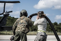 Airmen from the 33rd Rescue Squadron and the 18th Logistics Readiness Squadron lift a fuel hose to refuel an HH-60 Pavehawk during routine training on the flightline March 7, 2017, at Kadena Air Base, Japan. Aircrews rely on fuel from the 18th LRS to keep aircraft running and ready. (U.S. Air Force photo by Senior Airman Omari Bernard)