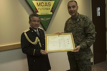 "Ginowan Police Chief Motoki Haneji, left, awards Col. Peter N. Lee with a letter of authorization Feb. 28 on Marine Corps Air Station Futenma, Okinawa, Japan. Lee was recognized by Haneji for the significant mutual support and cooperation between MCAS Futenma and the Ginowan City Police Department during the chief's command tenure. Haneji is retiring from his duties as chief of the Ginowan Police Department. ""Since the chief has arrived at Ginowan, we've had a great relationship with him, and because of him we've really enhanced the partnership between the station and the city,"" said Lee, the commanding officer of MCAS Futenma. ""Because of him we will continue to strive to be the best partners we can be."""