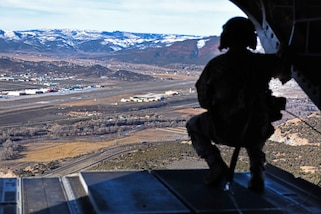 A South Carolina Army National Guard crew chief looks out the back ramp of a CH-47F Chinook helicopter for proper clearance while conducting high-altitude flight operations near Vail, Colo., March 10, 2017. Army National Guard photo by Staff Sgt. Roberto Di Giovine