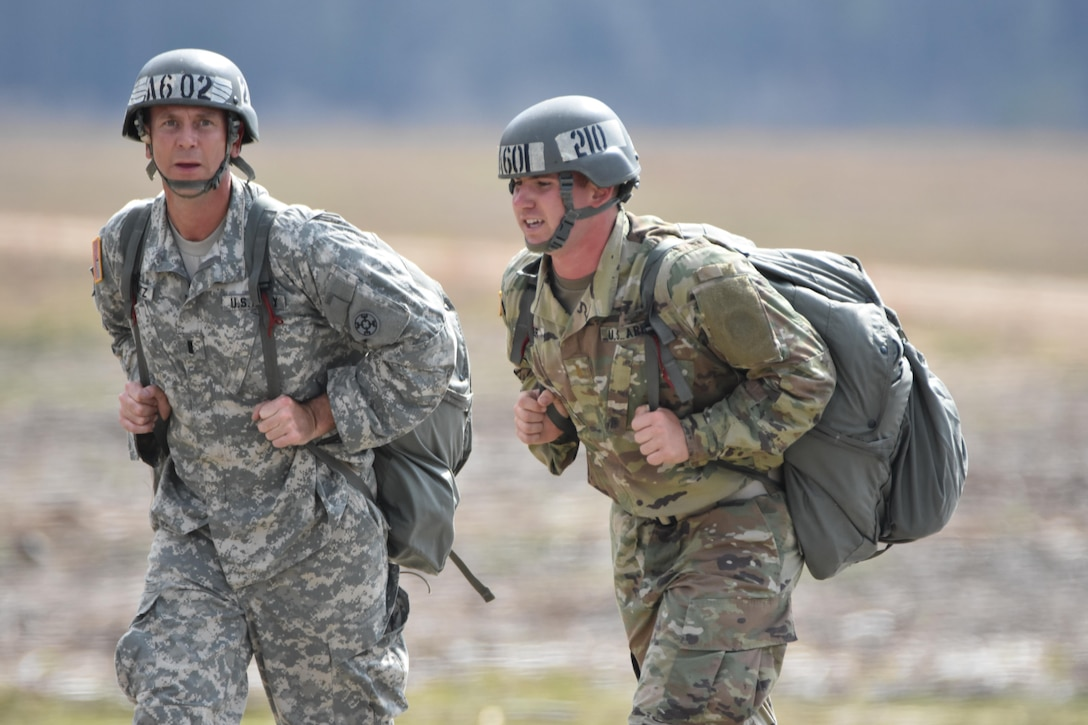 Army Reserve 1st Lt. Nicholas T. Krantz, commander of the 811th Ordnance Company, 321st Ordnance Battalion, 38th Regional Support Group, 310th Sustainment Command (Expeditionary), headquartered in Rainelle, W. Va., left, conducts airborne operations training at Fryar Drop Zone, Ft. Benning, Ga., Feb. 20, 2016.