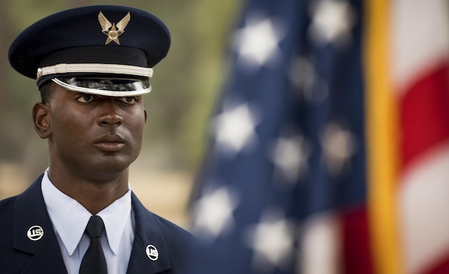 Kadeem Bell, 96th Force Support Squadron, stands by an American flag prior to the Honor Guard graduation ceremony at Eglin Air Force Base, Fla., March 1.  Approximately 12 new Airmen graduated from the 120-plus-hour course. The graduation performance includes flag detail, rifle volley, pall bearers and bugler for friends, family and unit commanders. (U.S. Air Force photo/Samuel King Jr.)