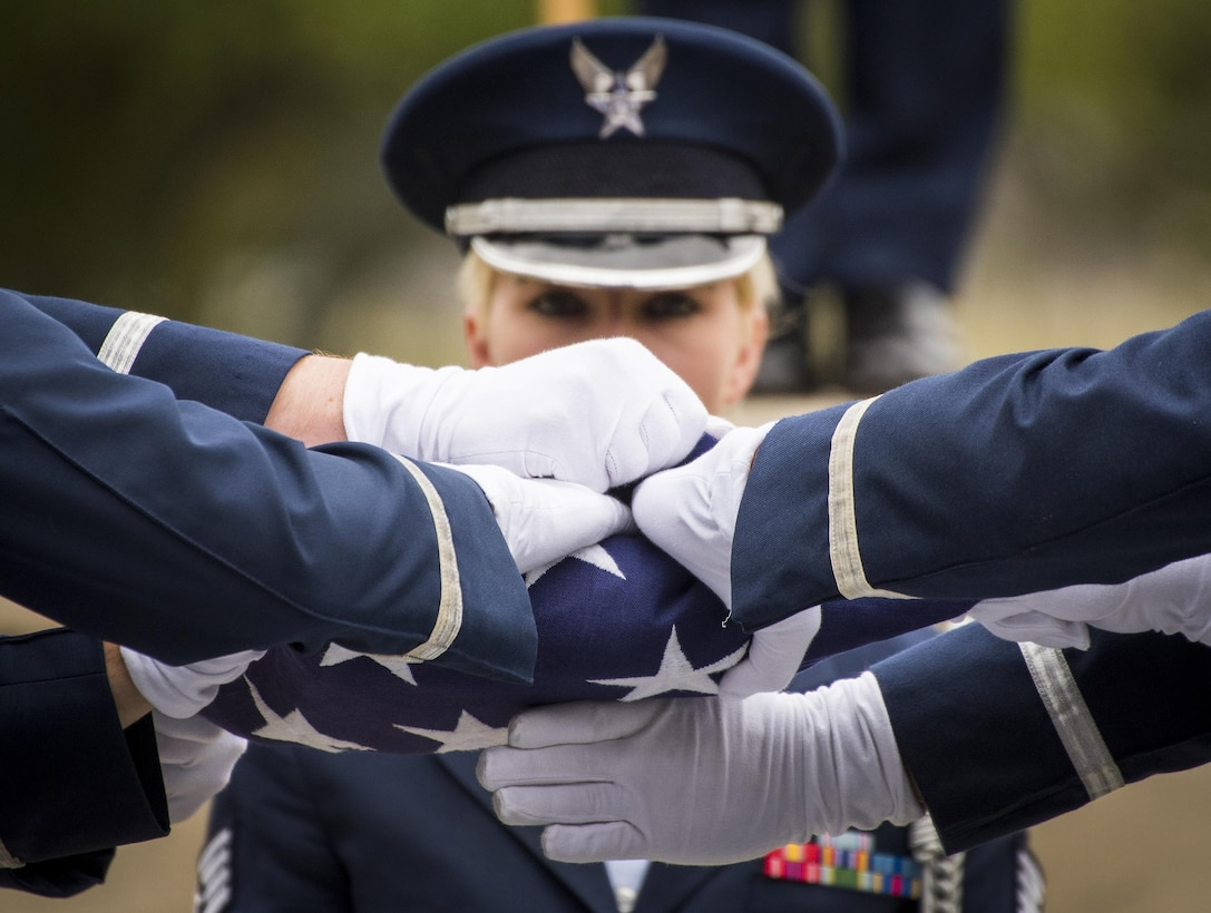 Honor Guard Airmen tighten and tuck in the rest of the American flag at the conclusion of the flag-folding portion at the unit's graduation ceremony at Eglin Air Force Base, Fla., March 1.  Approximately 12 new Airmen graduated from the 120-plus-hour course. The graduation performance includes flag detail, rifle volley, pall bearers and bugler for friends, family and unit commanders. (U.S. Air Force photo/Samuel King Jr.)