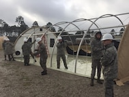 Under the supervision of a training cadre, emergency management personnel work with fire department personnel to erect a small shelter system during an exercise at Tyndall Air Force Base, Florida, January 22, 2017. The exercise was part of Silver Flag, a mandatory weeklong training exercise for certain civil engineer specialties in the military. (U.S. Air Force courtesy photo)