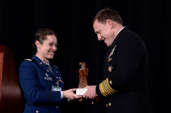 Cadet 1st Class Mary Simonton presents Adm. Mike Rogers, the commander of U.S. Cyber Command, with a token of appreciation for visiting the U.S. Air Force Academy March 14, 2017 and speaking at the Academy Assembly. Along with his Cyber Command duties, Rogers is the director of the National Security Agency and the chief of the Central Security Service. (U.S. Air Force photo/Mike Kaplan