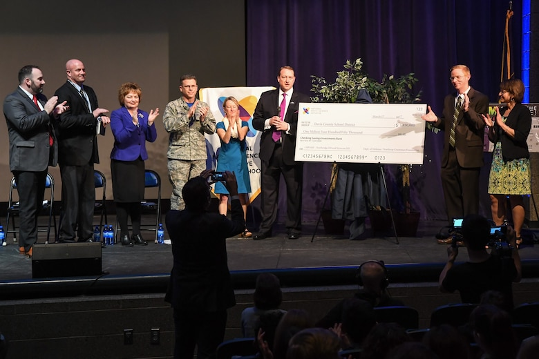 Officials from Hill Air Force Base, the Northrup Grumman Foundation, and the National Math + Science Initiative applaud after presenting multiple checks totaling $1.7 million for STEM education in the Davis School District during an event held at Syracuse High School, Utah, March 17, 2017. The majority of the investment will fund participation in the NMSI College Readiness Program at Northridge and Syracuse High Schools. The Department of Defense contributed $1.2 million, Northrup Grumman donated $250,000 and Hill AFB invested an additional $250,000 in partnership with the State of Utah STEM Action Center. (U.S. Air Force photo/ R. Nial Bradshaw)