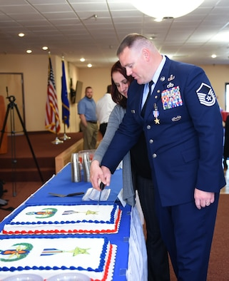 Retired U.S. Air Force Master Sgt. Kristopher Parker, an explosive disposal technician, and wife Zuzanna, cut Parker's Silver Star cake after his ceremony March 17, 2017, at Dyess Air Force Base, Texas. Parker distinguished himself by bravery and devotion to duty in connection with military operations against an armed enemy of the United States as an EOD team leader. (U.S. Air Force photo by Airman 1st Class Emily Copeland)