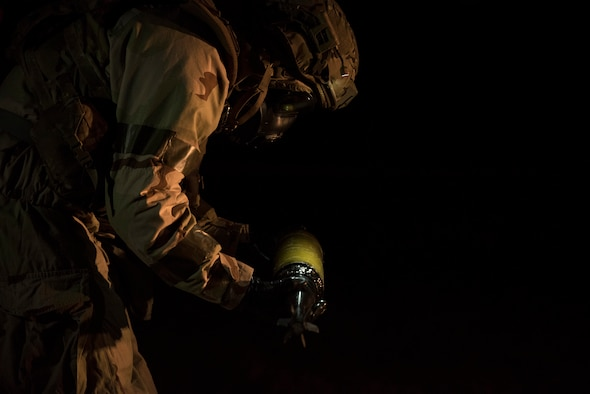Staff Sgt. Justin Smith, 23d Civil Engineer Squadron explosive ordinance disposal flight's NCO in charge of equipment, examines a simulated chemical bomb during a Mission Readiness Exercise, March 10, 2017, at Avon Park Air Force Range, Fla. The MRX took place March 2-13 and ensured the 822d Base Defense Squadron could efficiently deploy anywhere in the world in less than 72 hours. During the two week MRX, the squadron was evaluated on its ability to set-up a bare base, effectively thwart enemy attacks, run a secure Tactical Operation Center and maintain positive relationships with villagers in surrounding areas. (U.S. Air Force Photo by Airman 1st Class Janiqua P. Robinson)