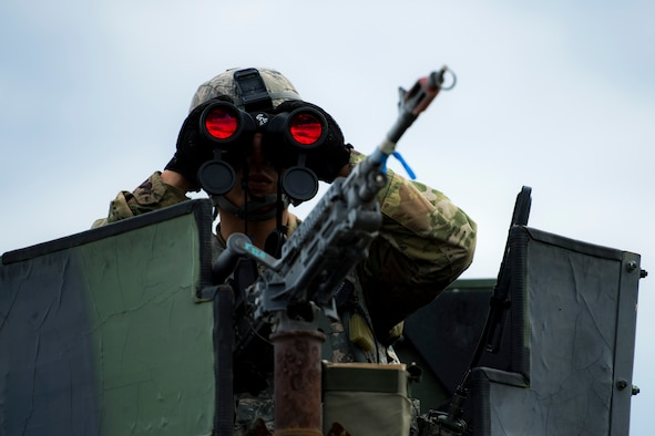 Airman 1st Class Chun Ko, 105th Base Defense Squadron fireteam member, looks into a nearby village to ensure there are no hostile villagers preparing to ambush is team during a Mission Readiness Exercise, March 8, 2017, at Avon Park Air Force Range, Fla. Airmen from the 105th BDS embedded into the 822d Base Defense Squadron to participate in the exercise. While the 822d BDS used the exercise to validate their training and regain their status as a Global Response Force, the 105th BDS received training that allowed them to show their capabilities and strengthened the bond between the two squadrons. (U.S. Air Force Photo by Airman 1st Class Janiqua P. Robinson)