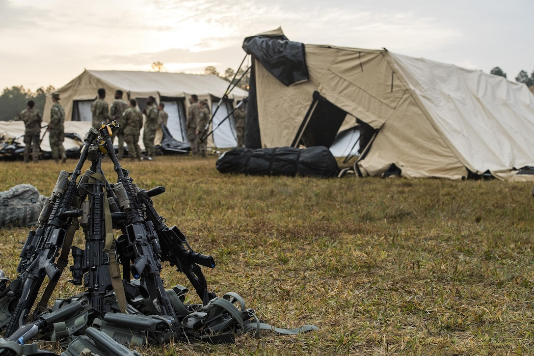 M4 Carbine Rifles rest in a stack while Airmen from the 105th Base Defense Squadron and 822d Base Defense Squadron break down tents at the end of a Mission Readiness Exercise, March 13, 2017, at Avon Park Air Force Range, Fla. Airmen from the 105th BDS embedded into the 822d BDS to participate in the exercise. While the 822d used the exercise to validate their training and regain their status as a Global Response Force, the 105th BDS received training that allowed them to show their capabilities and strengthened the bond between the two squadrons. (U.S. Air Force Photo by Airman 1st Class Janiqua P. Robinson)