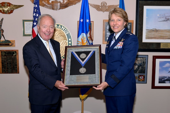Bill Hybl, the chairman of the Air Force Academy Foundation, accepts the 2015 Distinguished Service Award on behalf of the foundation, from Lt. Gen. Michelle Johnson, the superintendent of the U.S. Air Force Academy. (U.S. Air Force photo)