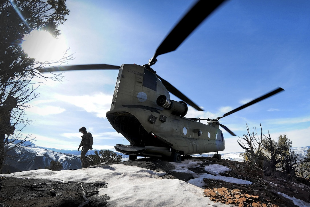 Two soldiers walk around a helicopter after landing on a mountaintop during high-altitude flight operations.