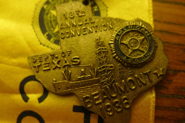 Pin identifying Leon Bell as a member of the reception committee for the 1936 American Legion conference in Beaumont, Texas, where he settled after the war. Medal depicts Spindletop oil well and a Navy ship being built in the local harbor.