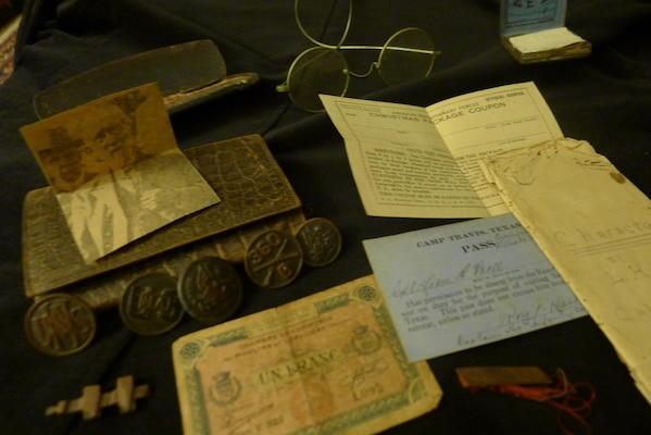 From left: French emergency currency; unidentified uniform insignia; Army uniform buttons, wallet; spectacles and case; newspaper photo of unidentified man, French cigarette rolling papers; label for Christmas package; liberty pass from Camp Travis, San Antonio; remains of medal or pin; 1913 essay on character.