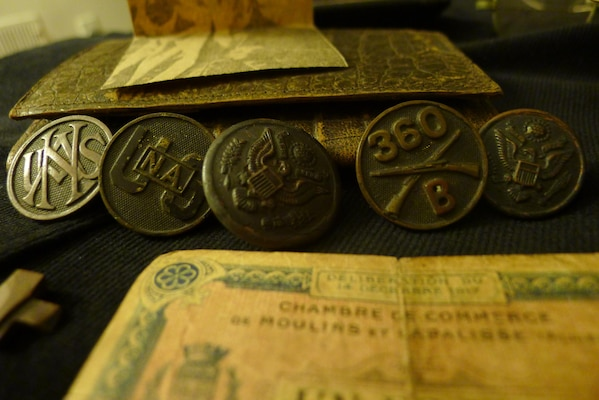 Close-up of uniform buttons, including U.S. National Army; provisional one-franc note from local French chamber of commerce in foreground.