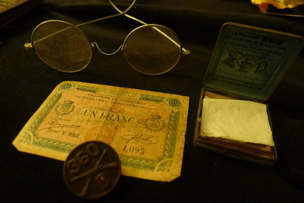 From bottom left: Items Sgt. Leon Bell brought home from WWI include a US Army 360th Infantry button, from his uniform coat; French provisional currency; wire-frame spectacles; and French cigarette rolling papers.
