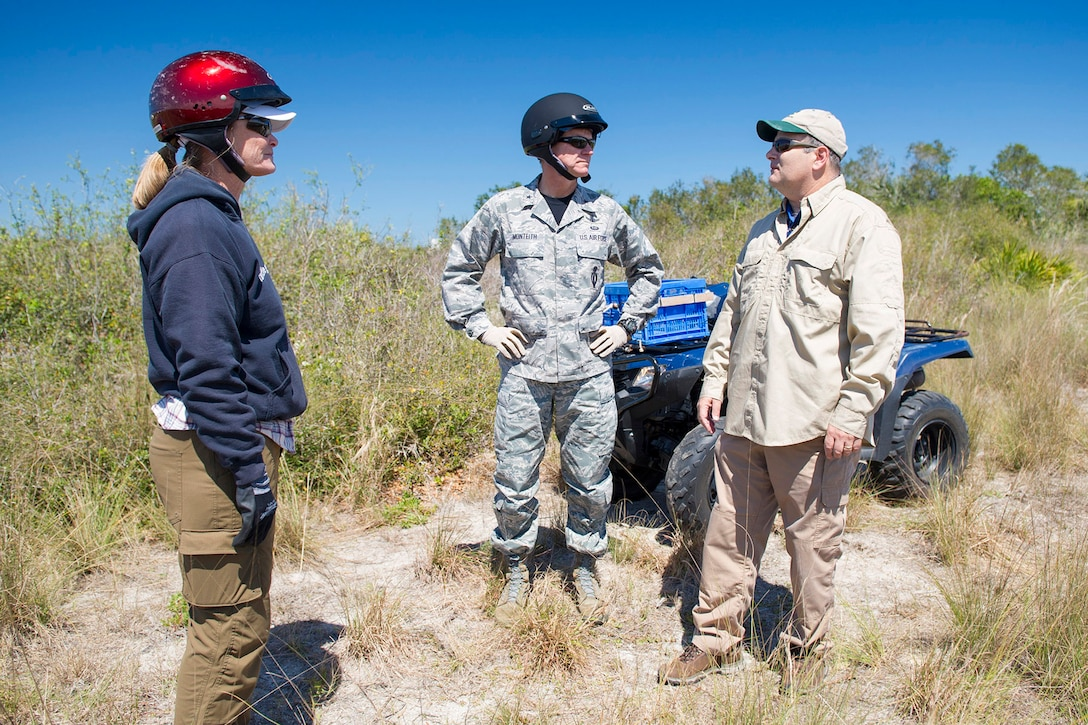 Angy Chambers, 45th Civil Engineer Squadron wildlife biologist, Brig. Gen. Wayne Monteith, 45th Space Wing commander, and Michael Blaylock, 45th Civil Engineer Squadron environmental conservation chief, discuss Florida scrub-jay habitat March 17, 2017, at Cape Canaveral Air Force Station, Fla., and how prescribed fire is an important tool in maintaining the habitat. The 45th environmental conservation office is responsible for the protection and integration of natural resources at the Cape and for the 45th Space Wing's mission. (U.S. Air Force photo/Matthew Jurgens)